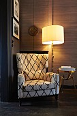Comfortable reading chair next to lit standard lamp and brass side table
