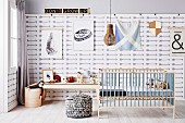 Children's room with cot and pouf, console table with toys in front of pattern wallpaper with arrow motifs