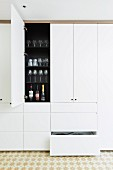 White, floor-to-ceiling built-in cupboard with drawers and open cupboard door in a kitchen