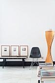 Schwarzer Klassikerstuhl neben Wandtisch mit gerahmten Bildern in Wohnraum mit minimalistischem Retro Flair