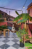 Abendstimmung über Terrasse mit Butterfly-Sessel und Pflanzentöpfe auf Marmor- Schachbrettmusterboden