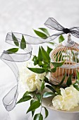 Black transparent ribbon draped around white carnations, leafy branches and ornamental birdcage