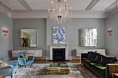 Herrschaftliches eklektisches Wohnzimmer mit Glas Couchtisch und Messing Untergestell vor Kamin, hellblaue Retro-Sessel und Sofa mit grünem Samtbezug