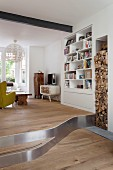 Eclectic living area on platform and firewood stacked in vertical niche next to white fitted shelves