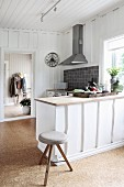 Kitchen counter and stools in country-house kitchen with white wood-clad walls and cork flooring