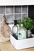 Bottled and potted herbs in marble box next to chopping board on kitchen worksurface