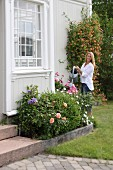 Woman watering flowers outside traditional country house