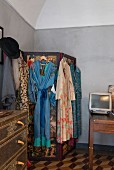 Kimonos hung from screen in corner of bedroom with vaulted ceiling