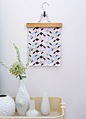 Graphic artwork hung from trouser hanger on wall