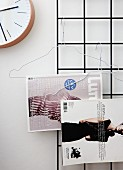 Magazines hung from wire coathangers on metal grid
