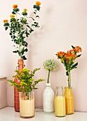 Blumen in mit Farbe gestalteten Flaschen und Gläsern