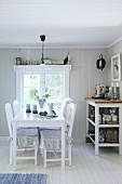 Essplatz am Fenster mit weißem Tisch und Stühlen neben Geschirrregal in Schwedenhaus
