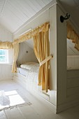 Yellow curtains and pelmets on cubby beds in wood-clad attic bedroom