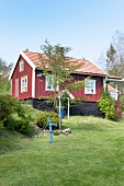 Falu-red Swedish house with white windows below blue sky