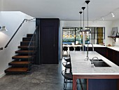 Counter with marble worksurface and staircase in open-plan kitchen