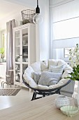 Cushions on comfortable papasan chair in bright interior with Scandinavian ambiance