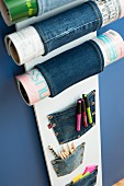 Magazine rack made from board and denim on blue wall