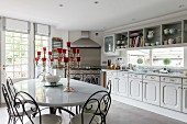 Metal dining chairs around silver candelabras on white table in front of country-house kitchen counter