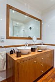 Custom wooden washstand below framed mirror on bathroom wall
