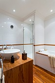 Exotic-wood washstand with white countertop basin opposite bathtub and shower