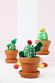 Blown eggs painted and decorated to look like cacti in terracotta pots