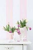 China Easter bunnies and vases of tulips in front of striped wallpaper