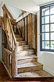 Rustic wooden staircase and lattice window in 18th-century farmhouse