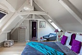 Wooden beams and colourful bed linen in attic bedroom