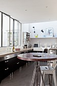 Black fitted kitchen with interior windows in loft apartment