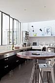 Schwarze Einbauküche mit Innenfenstern in Loft-Wohnung