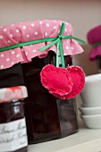 Jar of jam decorated with red and white polka-dot cover and hand-made cherry tag