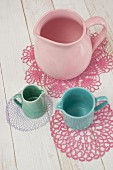 Various jugs on dyed lace doilies in pastel shades