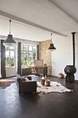 Wohnraum mit Kaminofen und anthrazitfarbenem Betonboden im Industriestil