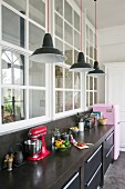 Black kitchen counter and pink fridge below interior windows in loft apartment