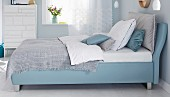 A boxspring bed in a bedroom in blue tones