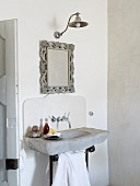 Tone sink with wall-mounted taps, mirror and wall-mounted lamp in simple bathroom