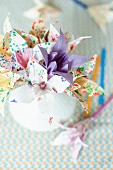 Artfully folded paper flowers made from origami paper of various patterns in vase