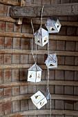 Girlande aus Miniaturhäuschen an Holzbalken aufgehängt