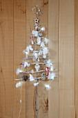 Selbstgebastelter Weihnachtsbaum aus dünnen Ästen, dekoriert mit Lichterkette, Federn und Baumanhängern, an Holzwand aufgehängt
