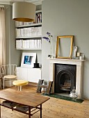 Fireplace next to fitted shelving in niche, grey-painted walls and wooden floor