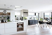 Dining area, black chairs and panoramic window in white, open-plan designer kitchen