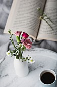 Open book, vase of flowers and cup of coffee on tray on bed