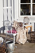Star-patterned blanket on comfortable white rocking chair on wooden terrace