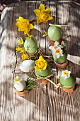 Painted Easter eggs used as vases for narcissus on old board