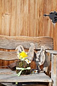 Two wooden hens and Easter flower arrangement on bench