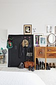 Coat pegs on chalkboard wall and shoes below dressing table with mirror