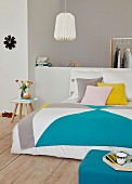 A tangram-style colourful quilt on a double bed