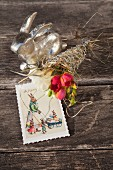 Silberner Osterhase neben Blumensträußchen und Postkarte
