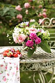 Romantic bouquet and fresh strawberries on vintage metal table in garden