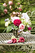 Romantic bouquet and knitted flowers on round, vintage metal table in garden